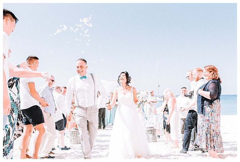 bride and groom walking through confetti throw at porto katskik beach lefkada
