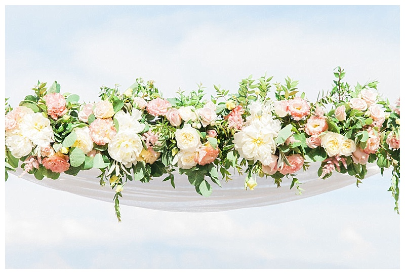 Close up of pastel coloured peonies and rosesflowers on top of a wedding arch