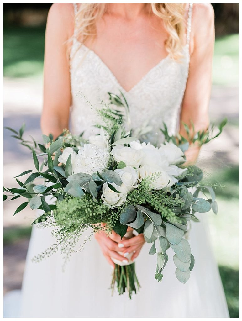 bride holding white peony and eucalyptus bouquet