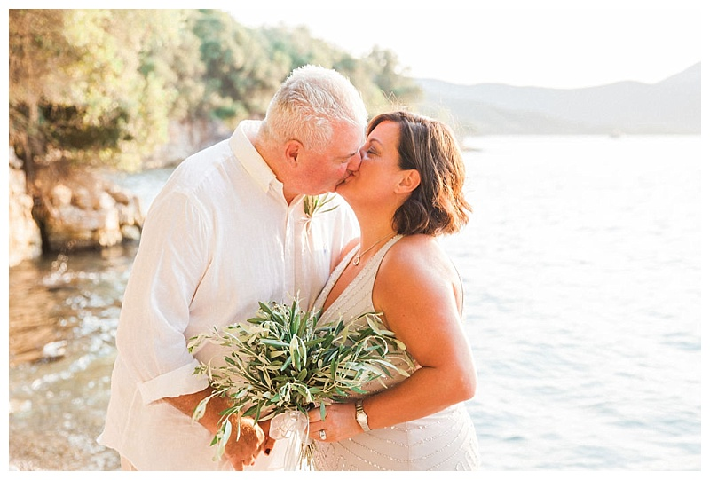 Couple kissing on beach, bride is holding a bouquet of olive leaves