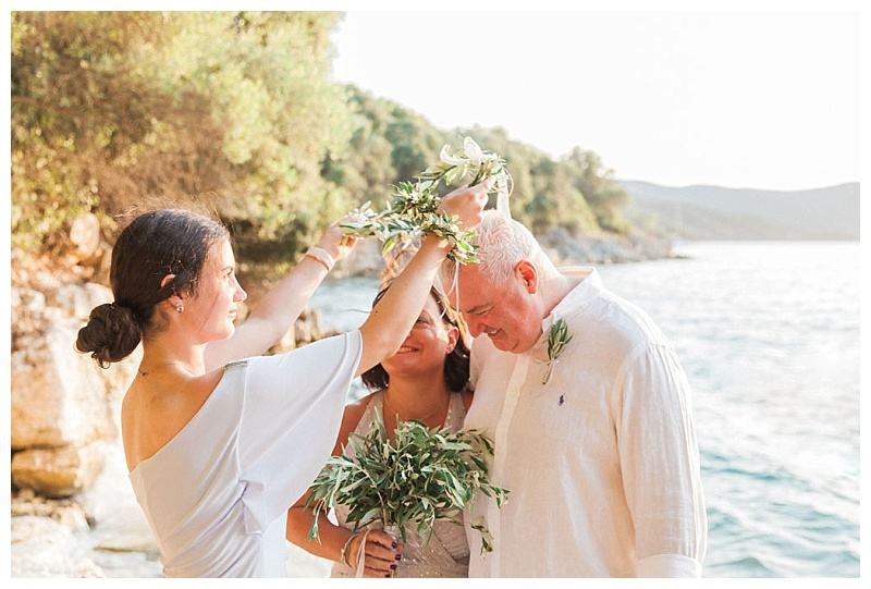 daughter placing olive wedding crowns on heads of her parents