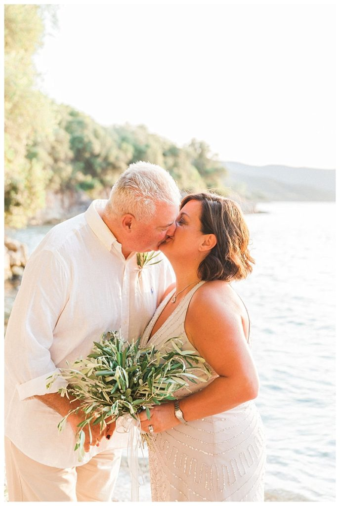 couple kissing on Meganisi beach with olive bouquet
