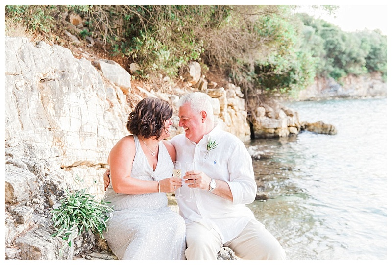 couple sat on rocks on Meganisi beach with champagne glasses
