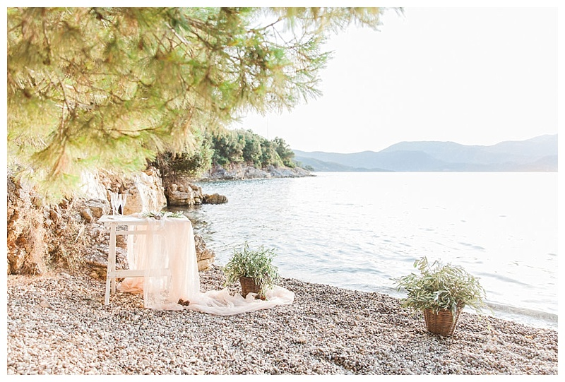 Table on pebble beach draped with fabric and decorated with baskets of olive