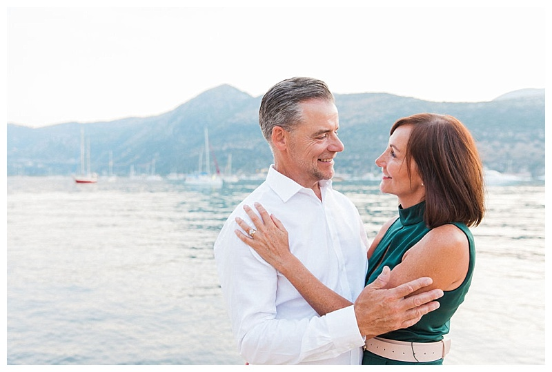 Couple smiling at each other with sea in background