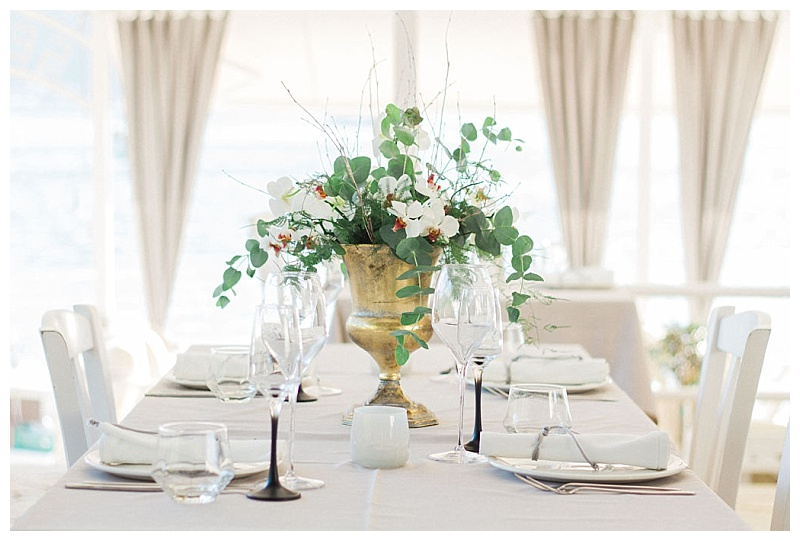 Table with grey linen at gold vase with white orchids