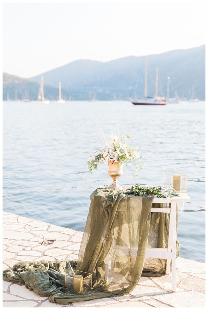 Decorated table with vase of orchids on terrace by sea for vow renewal ceremony