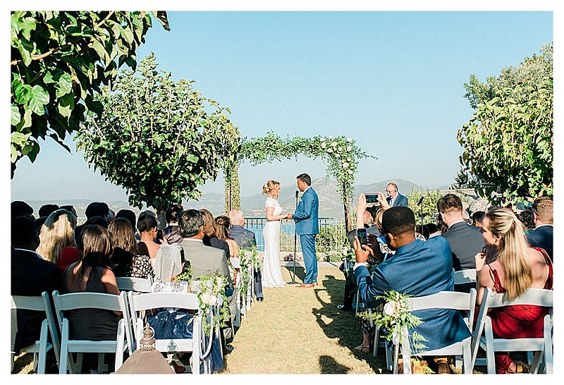 bride and groom standing under arch at garden ceremony in greece