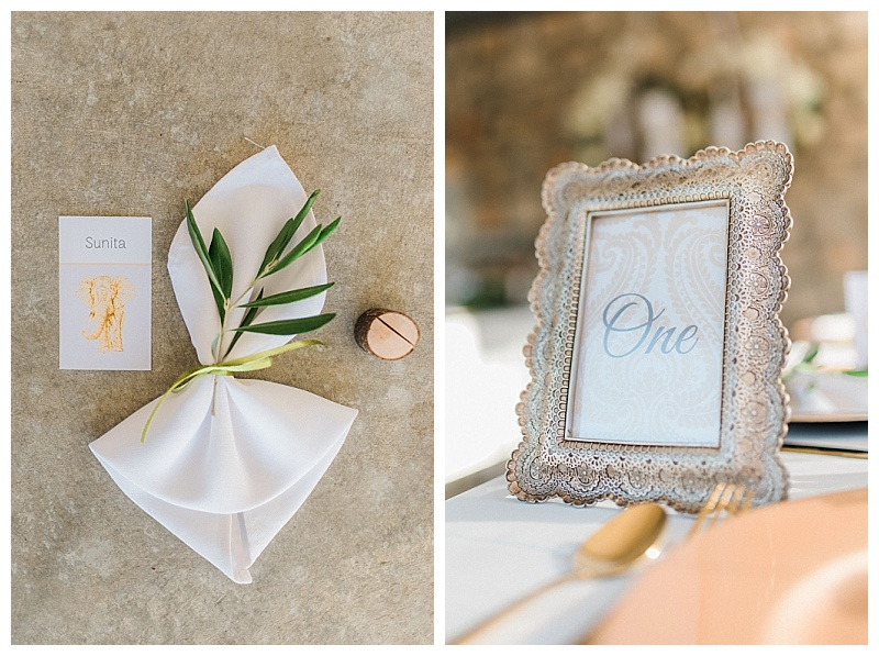 filigree detail gold frame with wedding table number, napkin tied with olive and indian inspired gold elephant place name card
