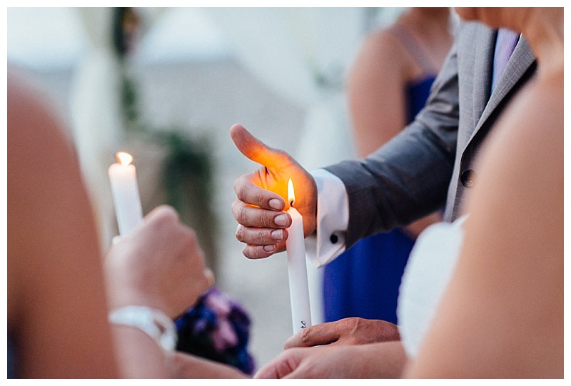 bride and groom lighting lighting candles at beach wedding ceremony