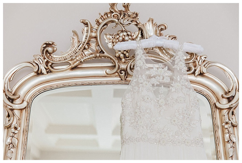 Illusion bodice of wedding dress hangin against a gold ornate mirror
