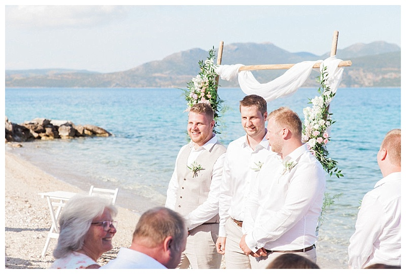 groom with excited look on face standing with ushers in front of flower arch on the beach