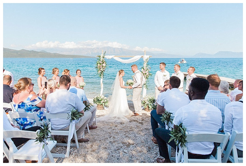 panoramic view down aisle of beach wedding ceremony with floral arch