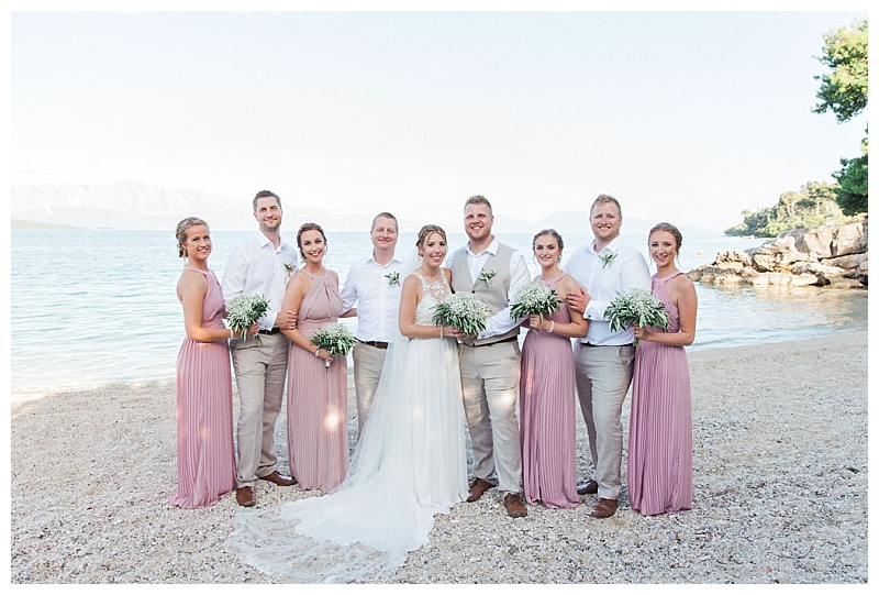 bride and groom with ushers and bridesmaids in lilac dresses group shot at private beach wedding in lefkada greece