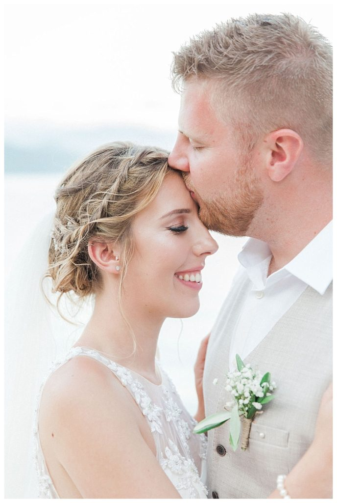 groom kissing brides forehead