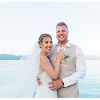 bride and grrom standing side by side on jetty by sea smiling at camera