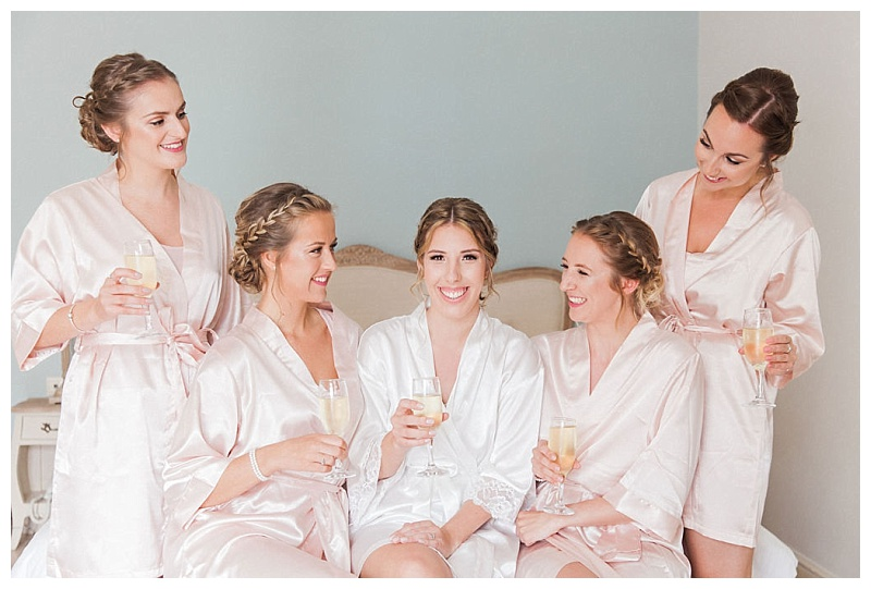 bride and bridesmaids sat on bed in dressing gowns drinking champagne