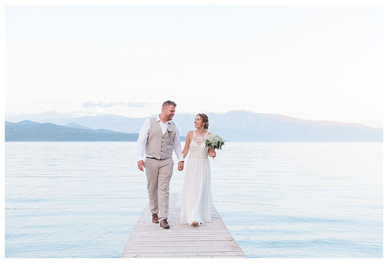 wedding couple walking on private beach jetty