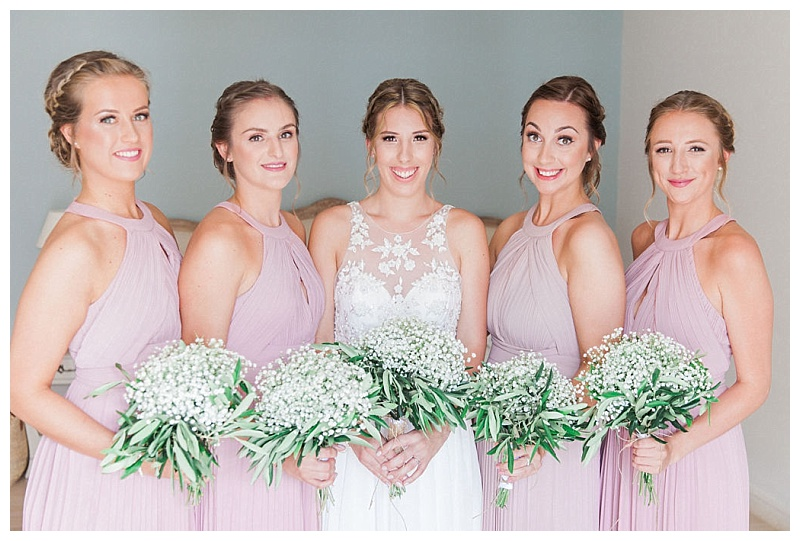 bride and four bridesmaids in lilac dresses all holding gypsophila bouquets