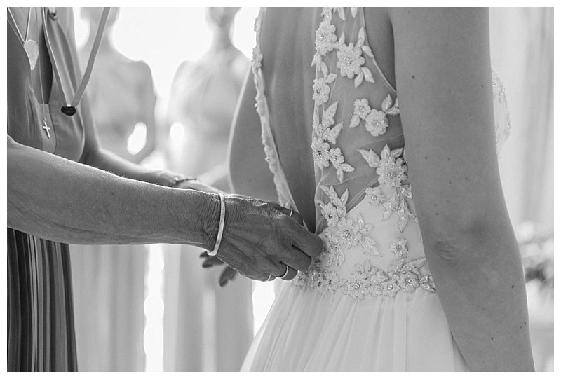 black and white image of fastending of bride's dress before wedding