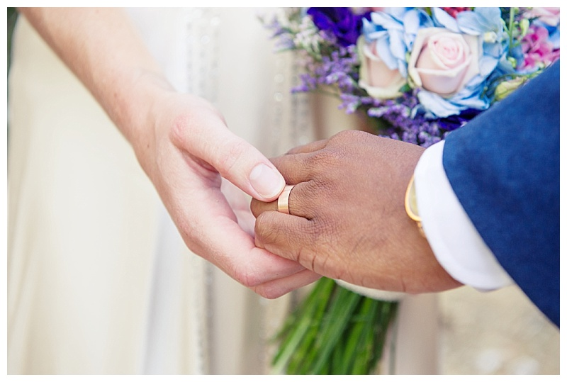 bride and groom hands joined with bright bouquet