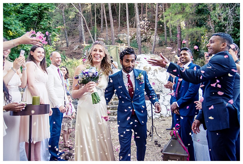 colourful confetti shot with newly married couple at woodland wedding