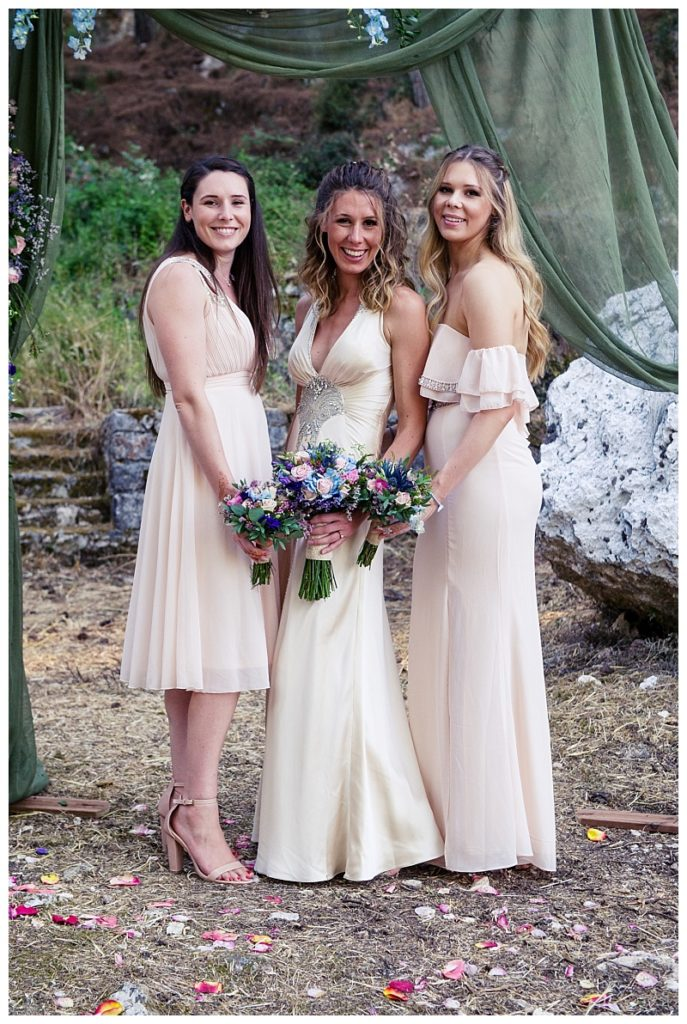 bride in oyster satin dress with bridesmaids standing either side