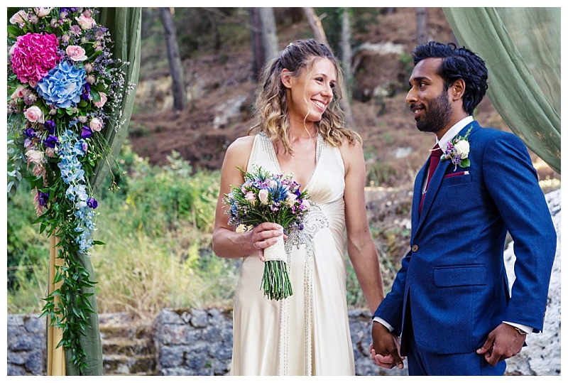 bride in oyster dress holding bright bouquet and groom in navy suit