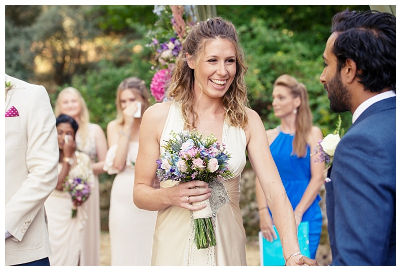 bride in oyster dress holding bright bouquet and groom in navy suit woodland ceremony