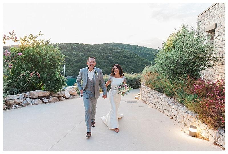 bride and groom walking hand in hand through hotel gardens greece