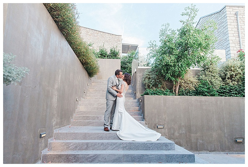 bride and groom embracing with modern concrete stairway backdrop