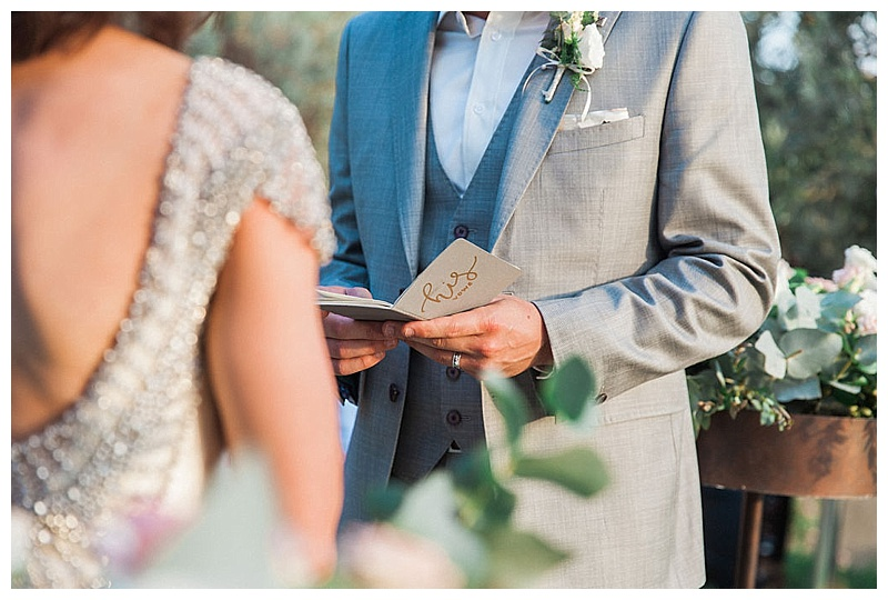 groom holding vow book at wedding ceremony