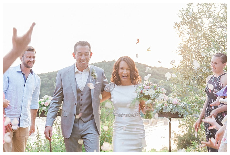 sun flare image of bride and groom walking through shower of rose petals