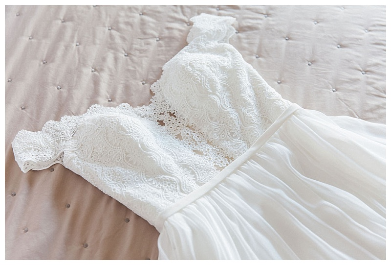 close up of bodice of bridal gown lying on bed