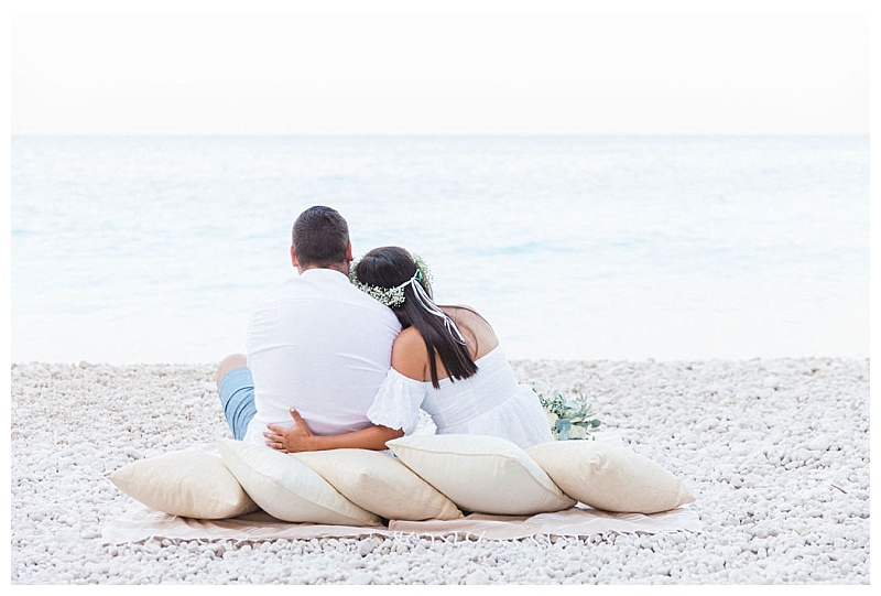 back view of couple sat on white stone beach with cushions looking out to sea
