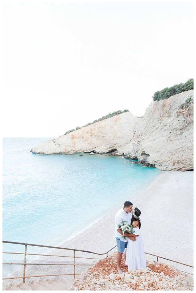 bride and groom kissing on stairs above porto katsiki beach lefkada