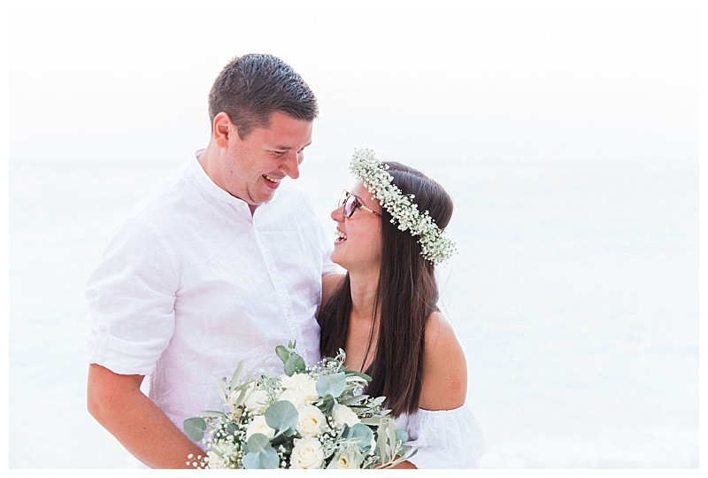 bride with glasses holding white and green flowers laughing with groom with arms around each other