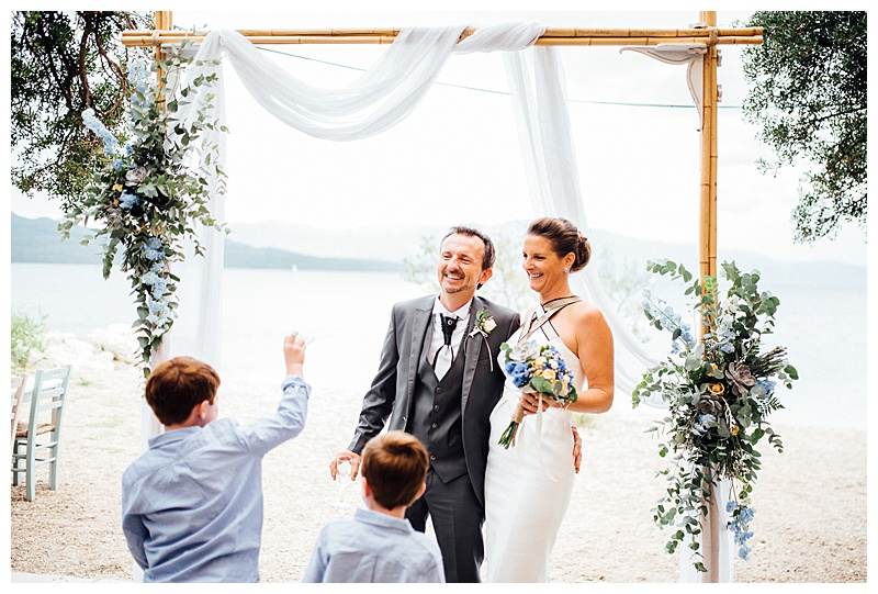 bride and groom laughing under arch whilst confetti thrown by children