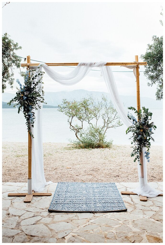 wedding arch in front of beach with blue and green floral decoration