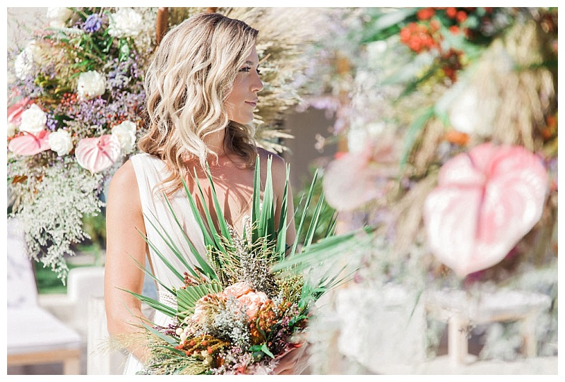 Bride iwht shoulder length wavy hair holding tropical bouquet