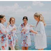 Bride and bridesmaids in floral dressing gowns drinking champagne on villa balcony in Greece