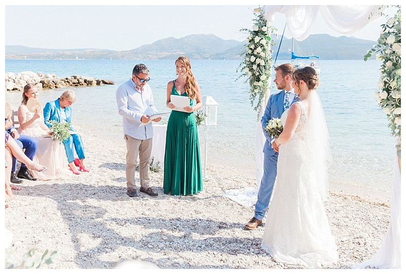 Lefkada wedding planner Claire Salisbury of Lefkas Weddings in a green dress reading ceremony script with wedding couple on a beach